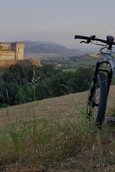 Una E-bike e sullo sfondo il castello diTorrechiara